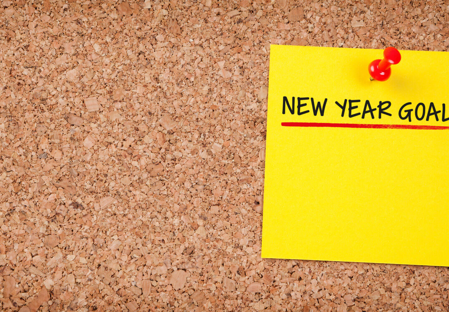 post-it note on a corkboard that reads new year goals