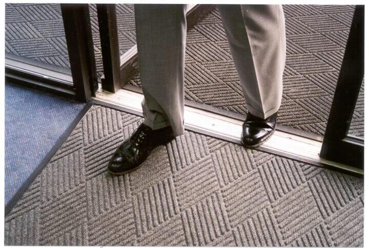 person stepping through door with a waterhog mat under foot