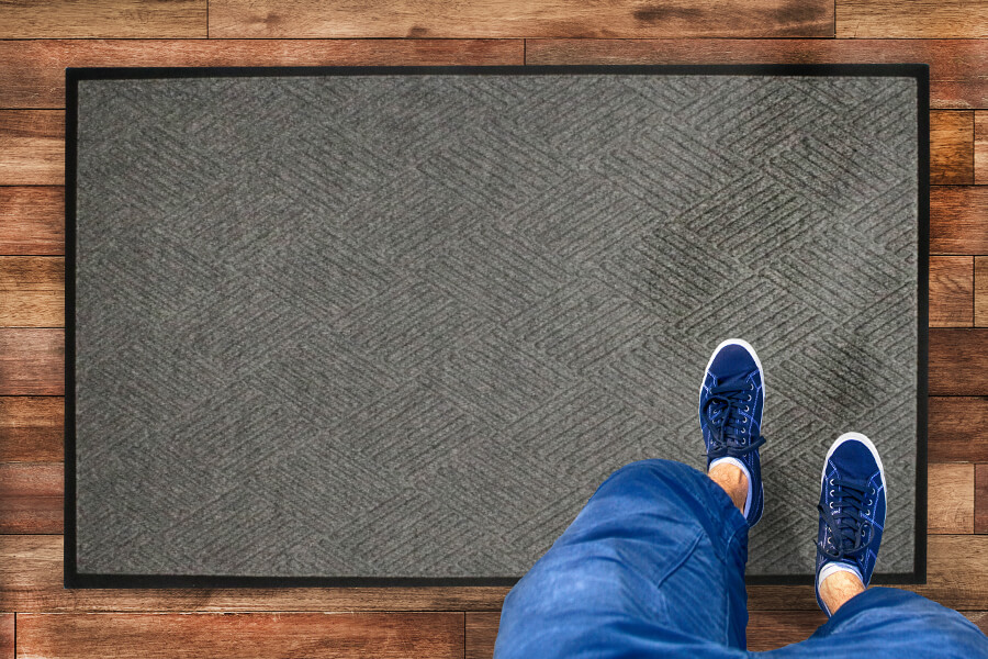 a person standing on a waterhog mat with diamond pattern
