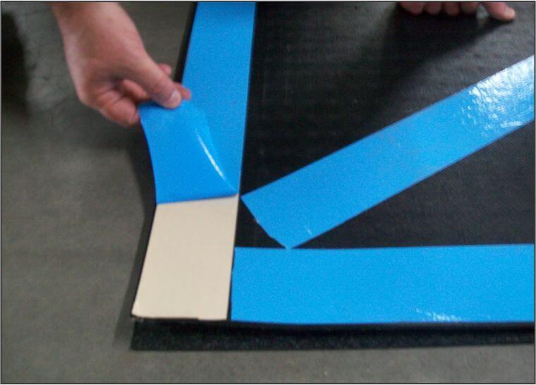 person peeling away blue tape